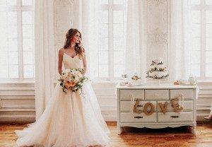 Image of bride holding a boutique of flowers standing next to a dresser with the words love on it