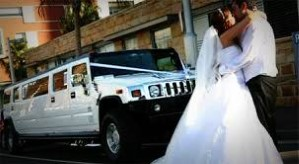 Image bride and groom hugging and kissing in front of a white New Haven H2 Hummer