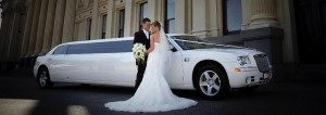 Image of bride and groom in front of white Norwalk wedding limousine