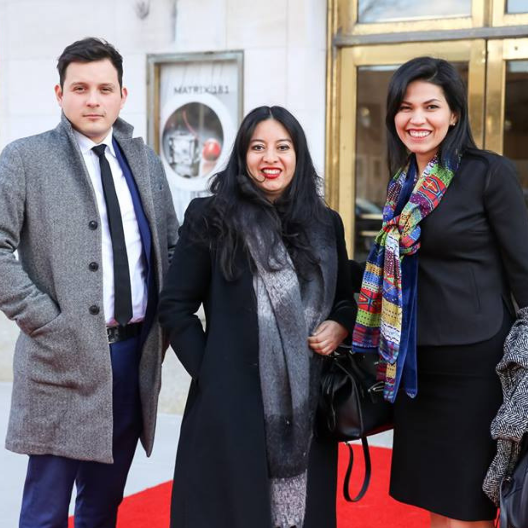 Three people standing on red carpet