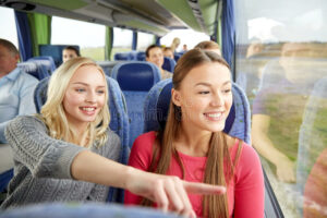 happy-young-women-riding-travel-bus-transport-tourism-friendship-road-trip-people-concept-teenage-friends-66926477