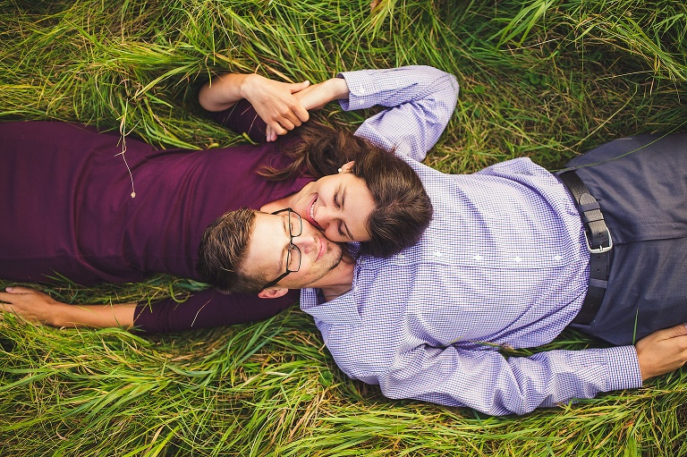 couple laying in grassing and smiling in freeland michigan