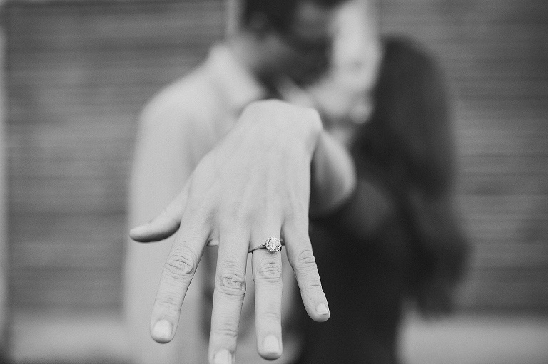 couple kissing and showing wedding ring