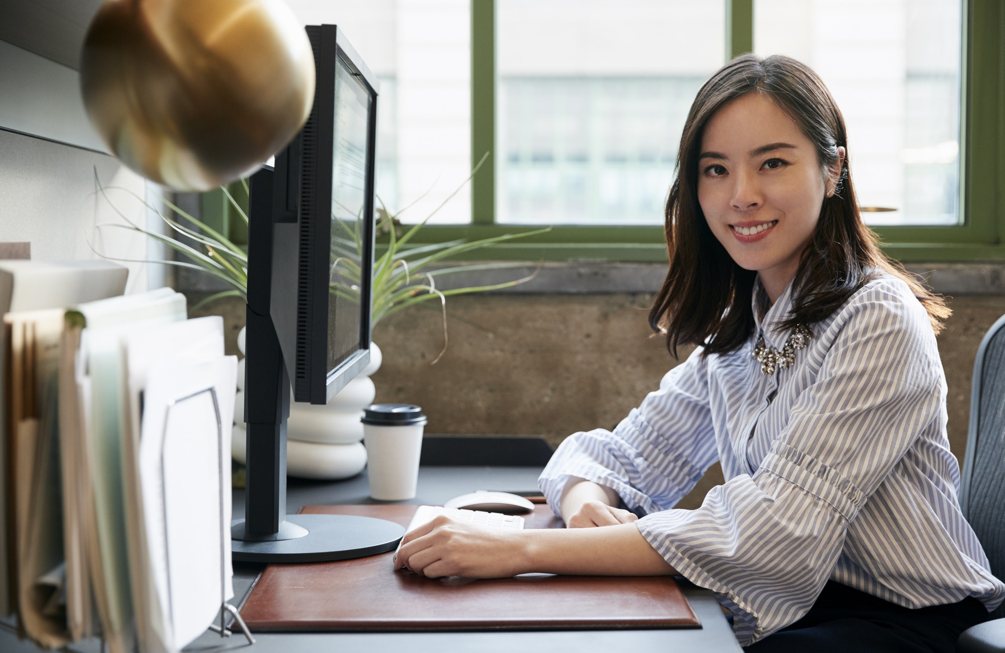 Chinese woman at a computer in an office smiling to camera