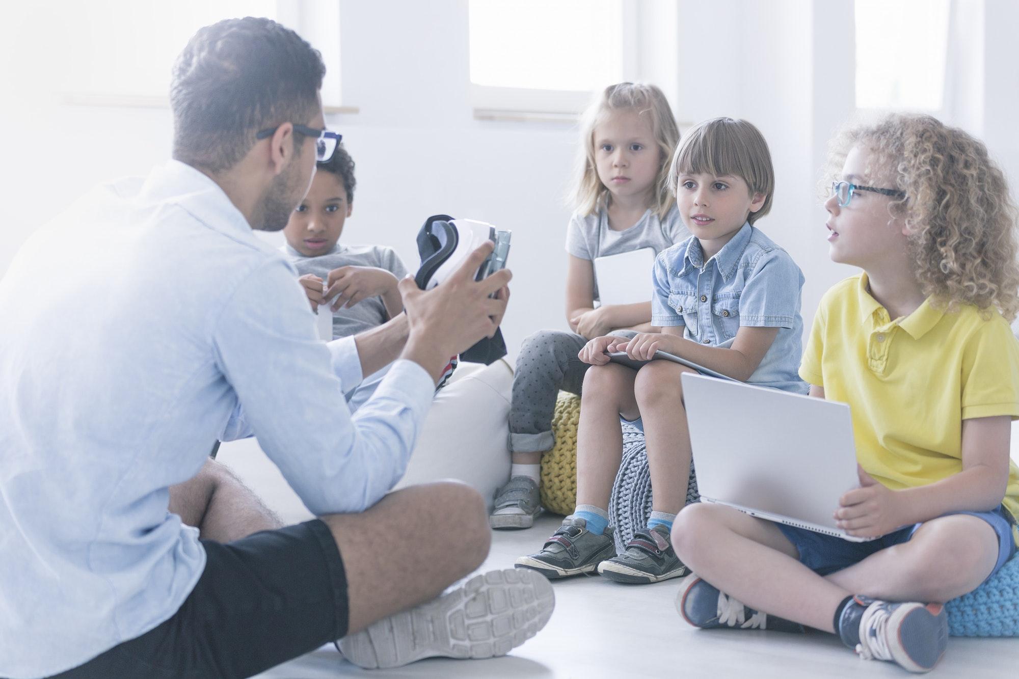 Happy teacher shows children the robot