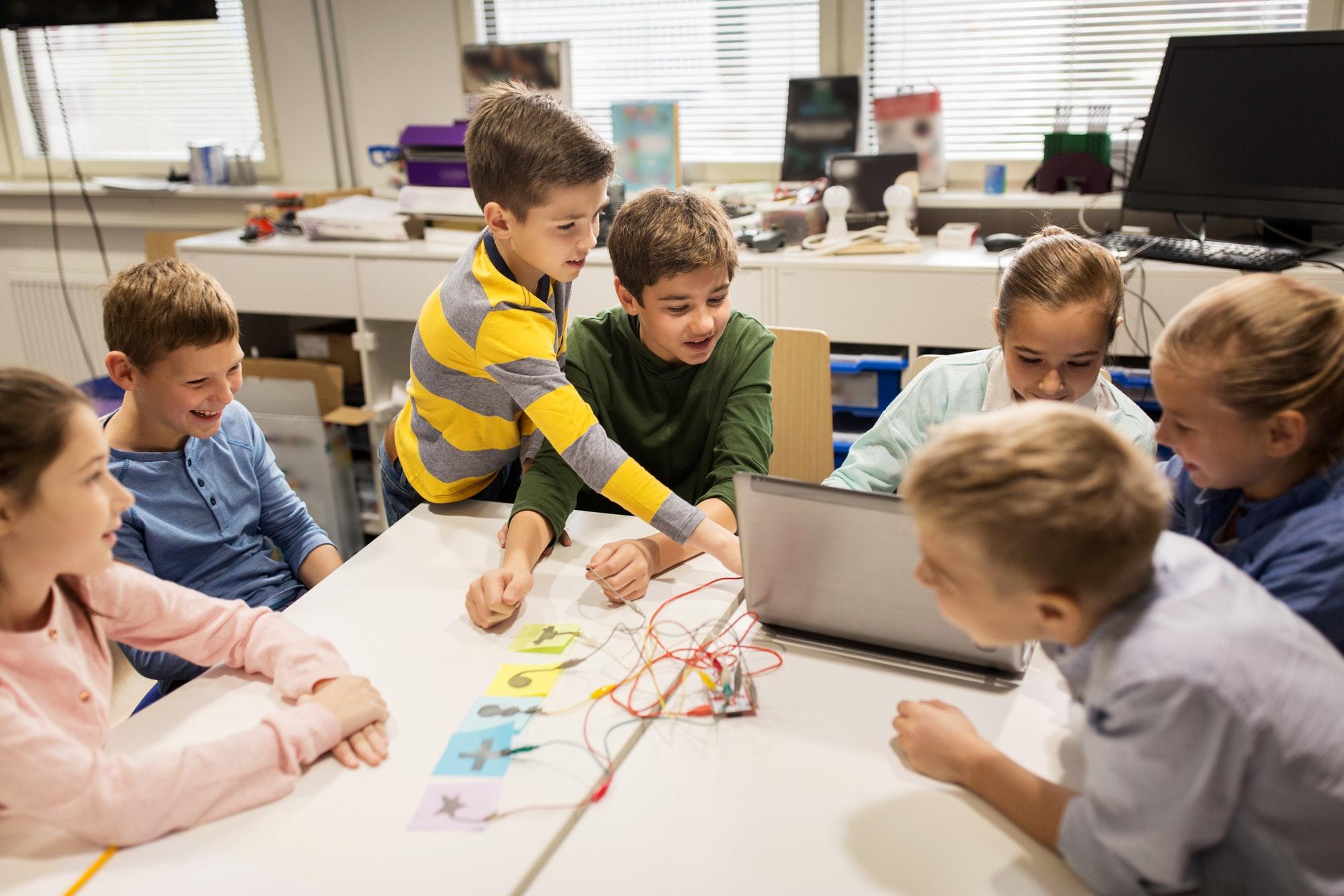 kids, laptop and invention kit at robotics school