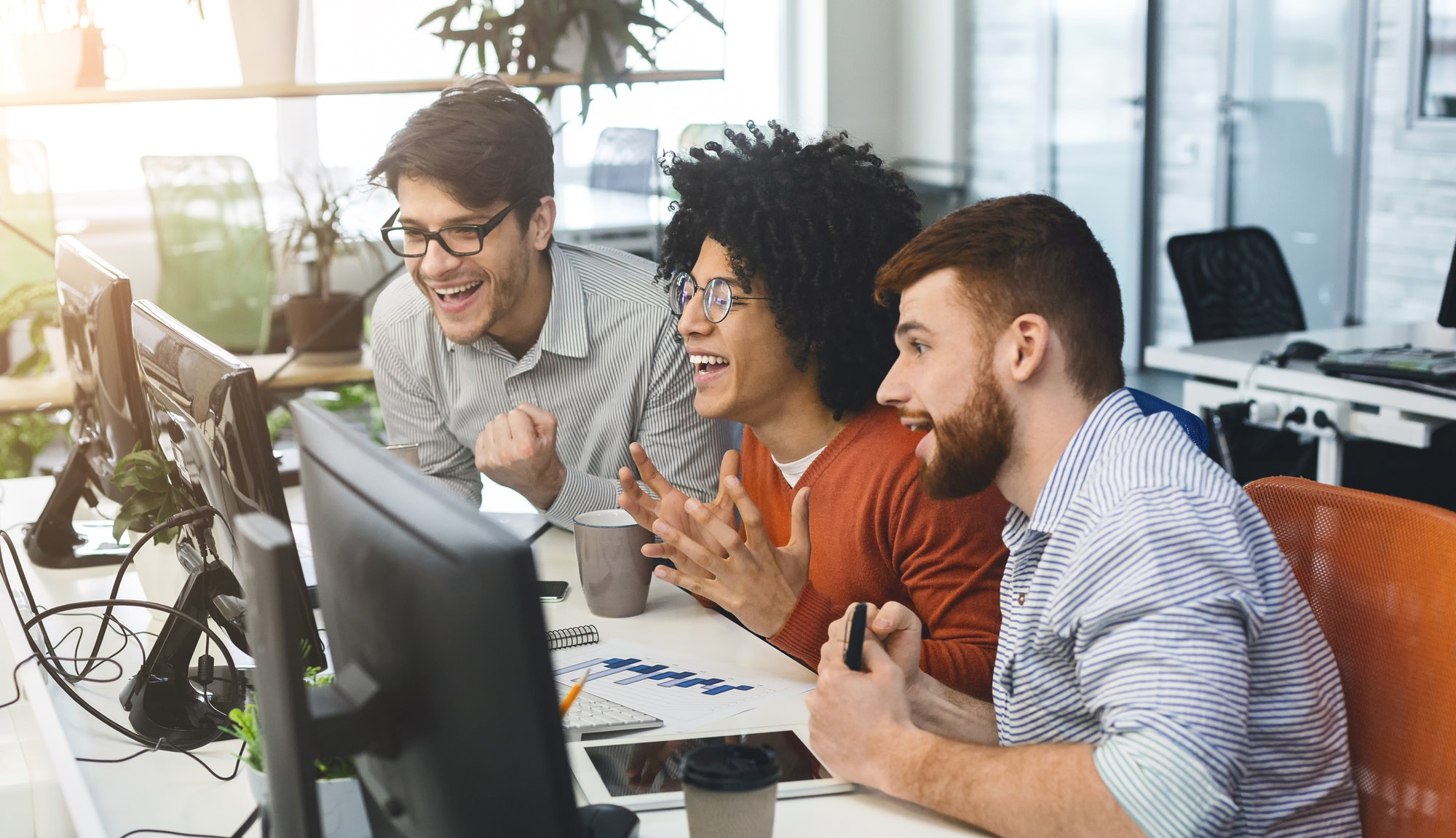 Three young men enjoying good coding job on computer