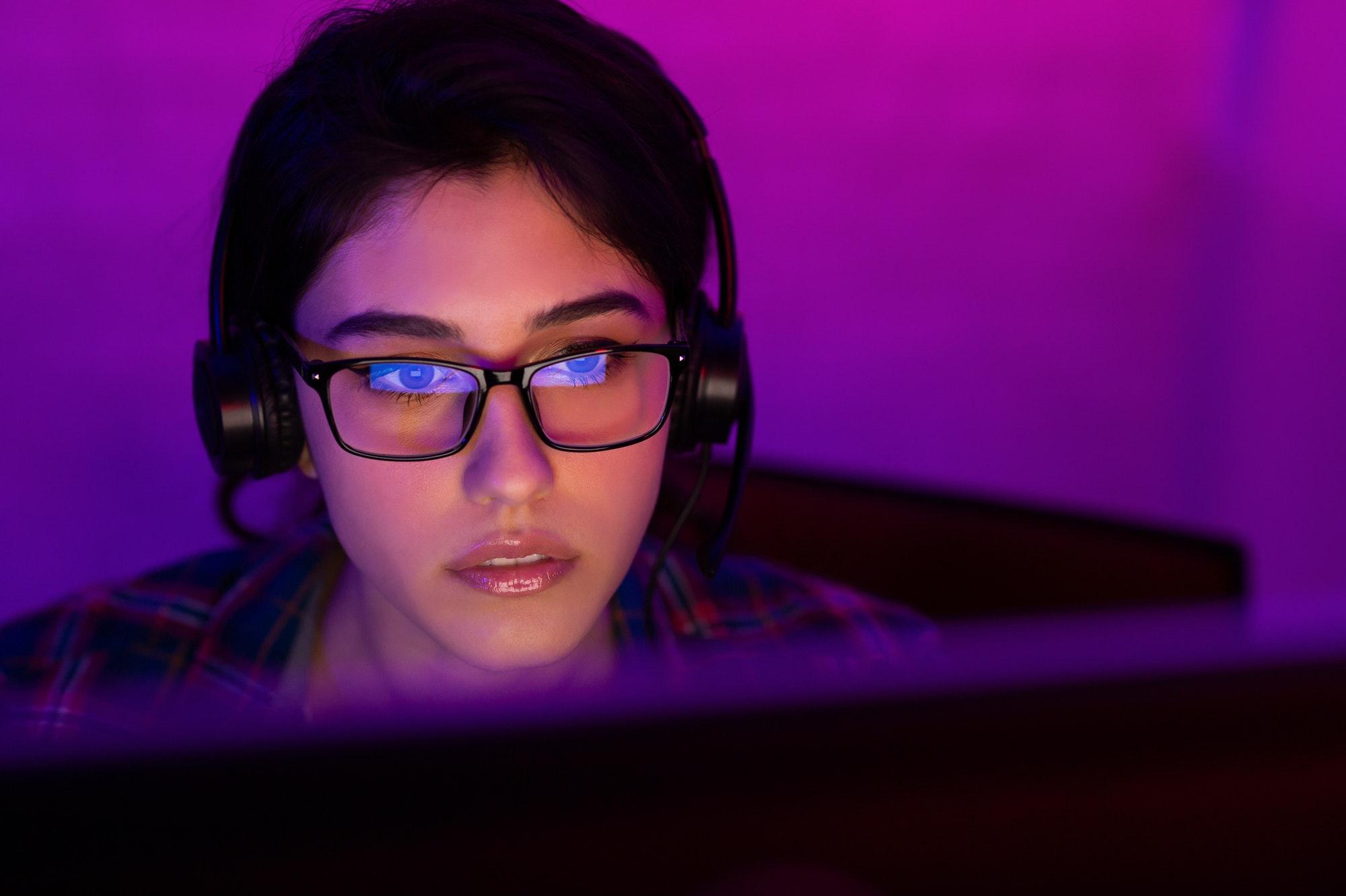 Female gamer in eyeglasses streaming online playthrough video