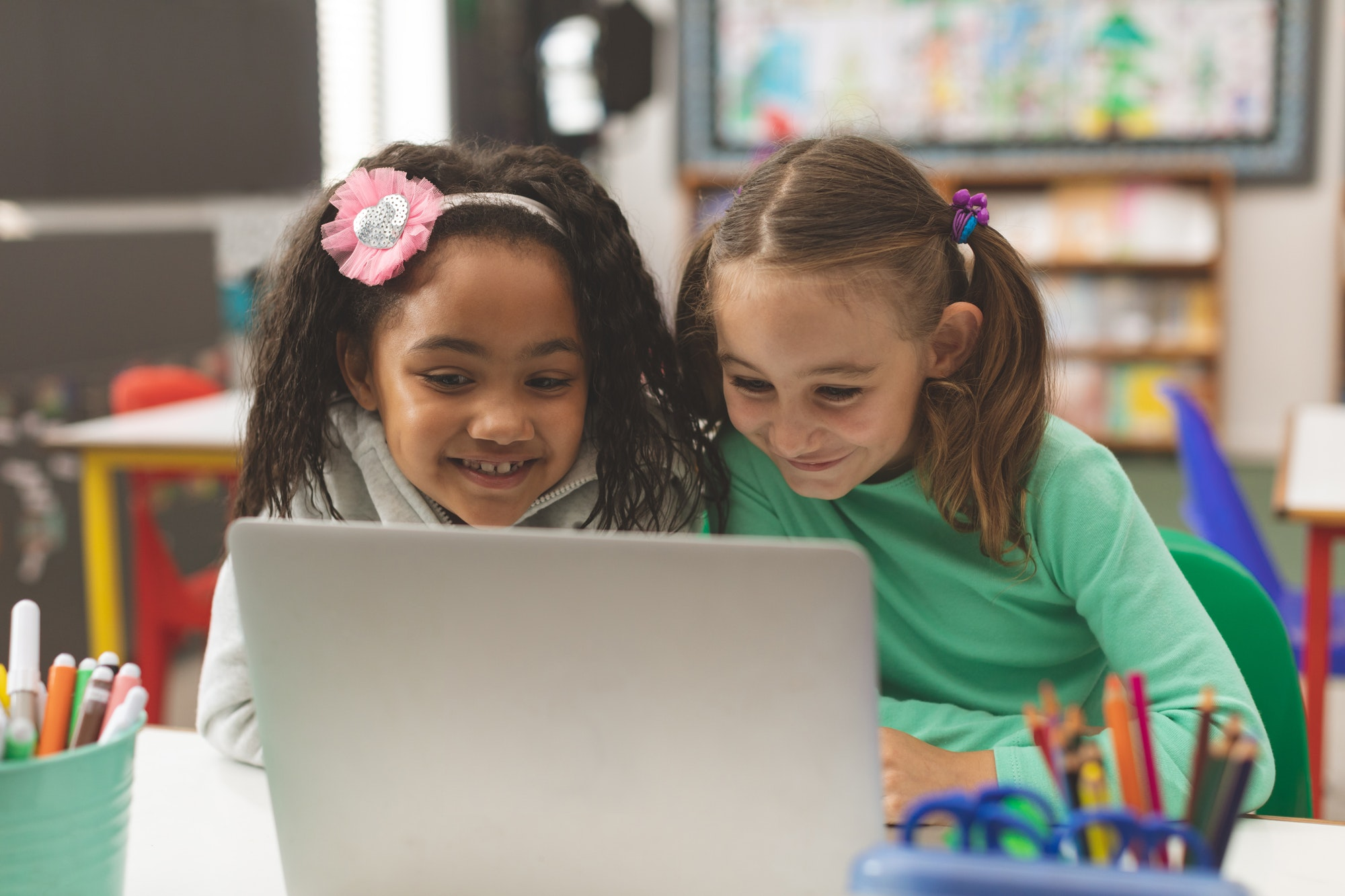 Schoolgirl smiling while they working on their computer in classroom at school