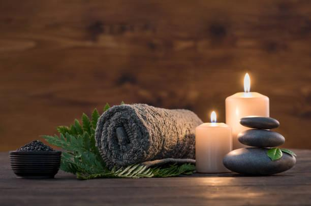 Brown towel on green fern with candles and black hot stone on wooden background. Hot stone massage setting lit by candles. Hot stone therapy for one person with candle light. Beauty spa treatment and relax concept.
