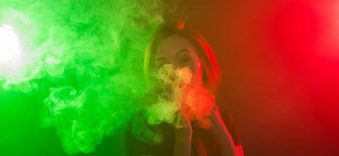 Portrait of girl in colored neon smoke with vape or electronic cigarette.