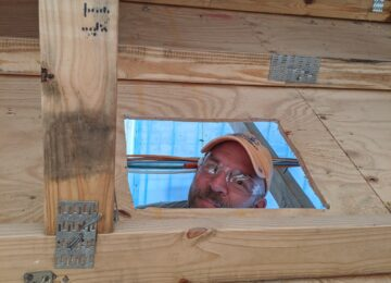 Construction worker peeking through wood
