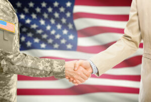 Military personnel shaking hands with a civilian business person