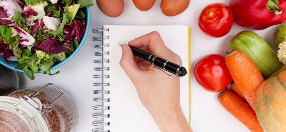 An image depicting a dietitian writing in a notebook.