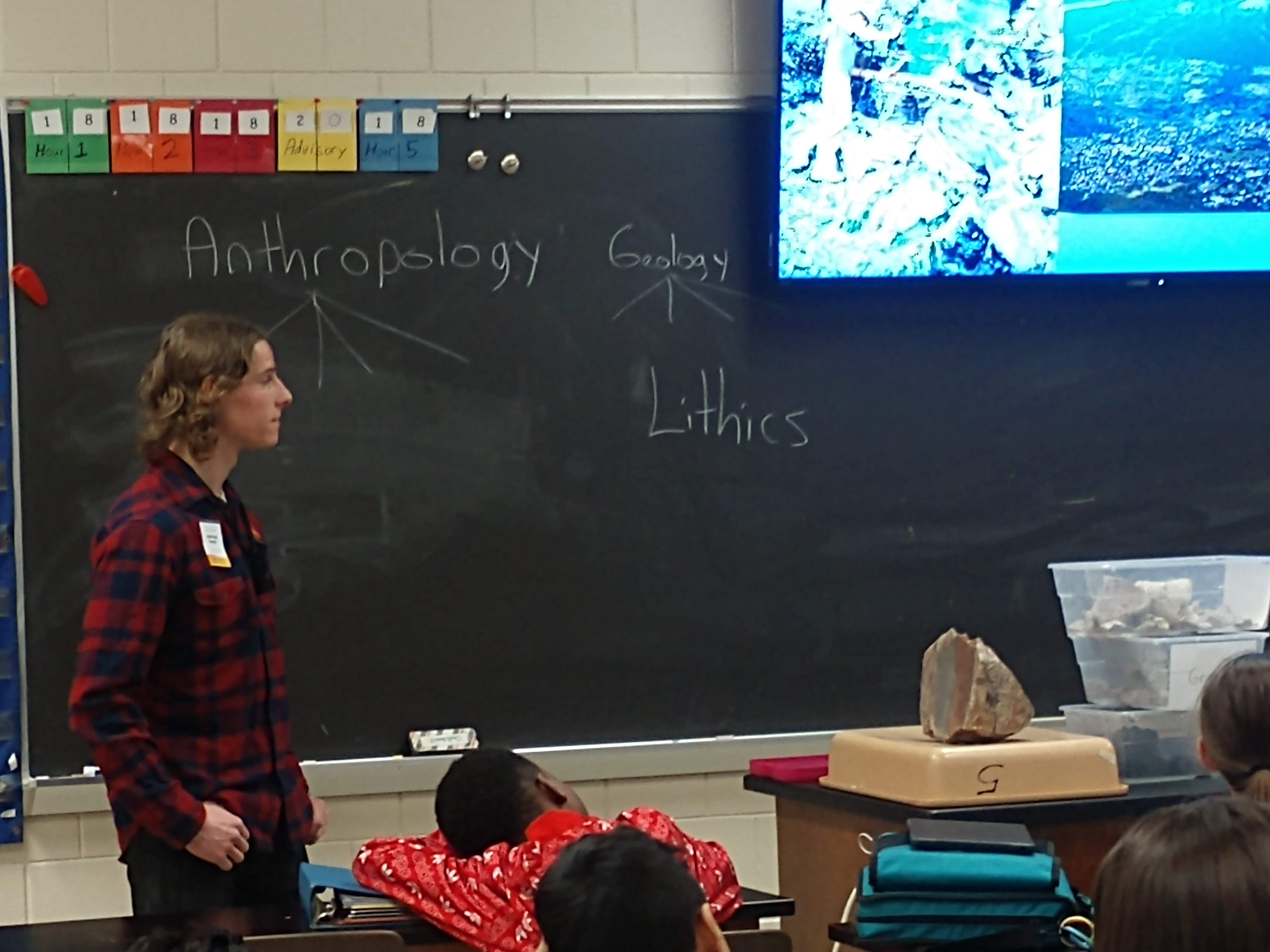 """Michael stands at the front of a classroom with young students with """"anthropology"""" and """"geology"""" written on the chalkboard."""