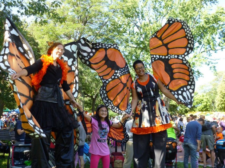 Photo showing two people standing high on stilts, dressed as monarch butterflies with large orange, black, and white wings, and an excited child, also wearing wings, standing between them.