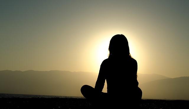 Women practicing presence and enjoying a sunrise