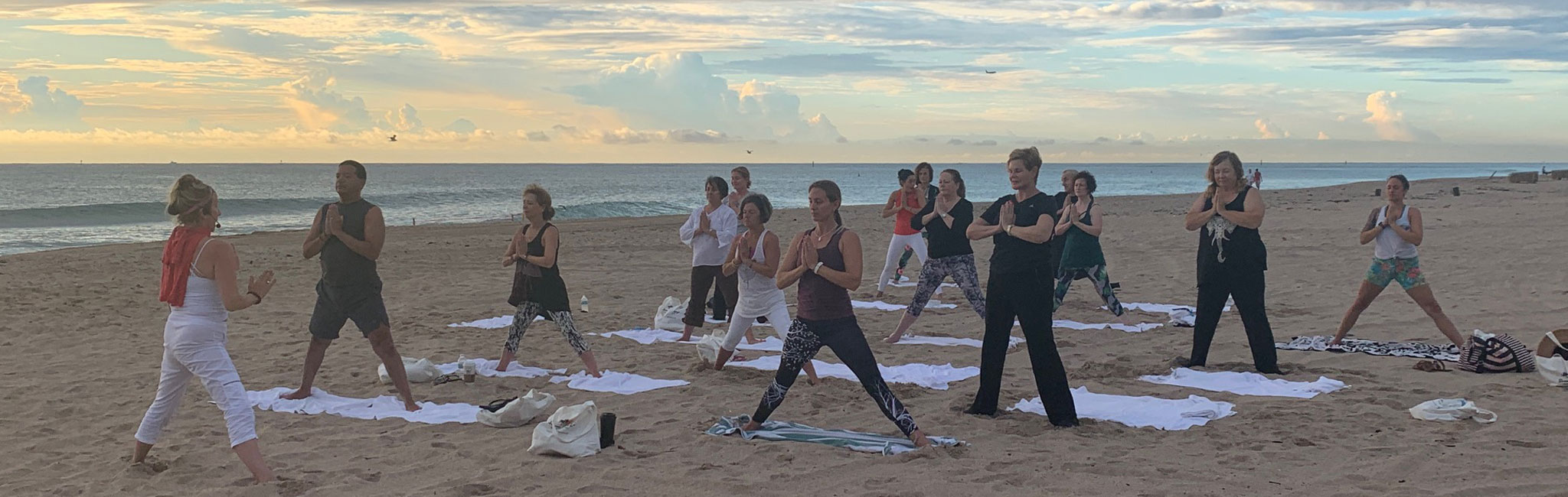 View of yoga class on the beach copying their instructor