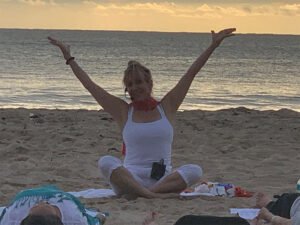 View of yoga teacher stretching her arms up to the sky