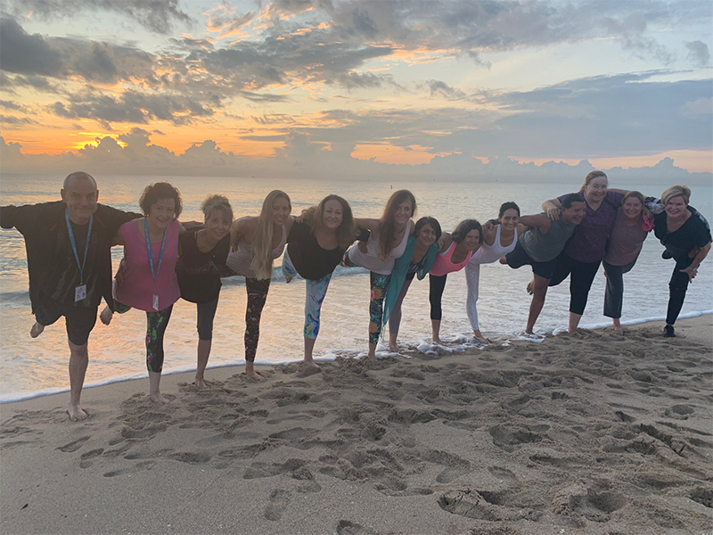 Stress Less Yoga Retreat - 12 people in a yoga pose on the beach at sunrise