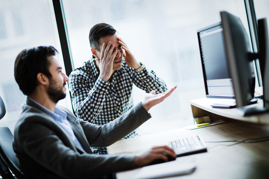 Business colleagues working on computer and having problems