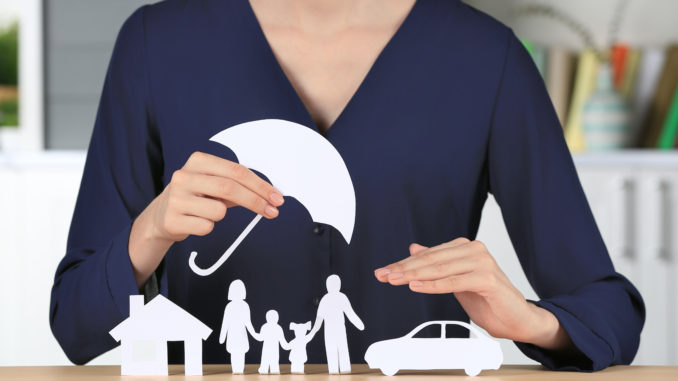 person with paper umbrella over paper home family and car