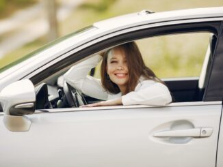 Teen girl driving in a white car