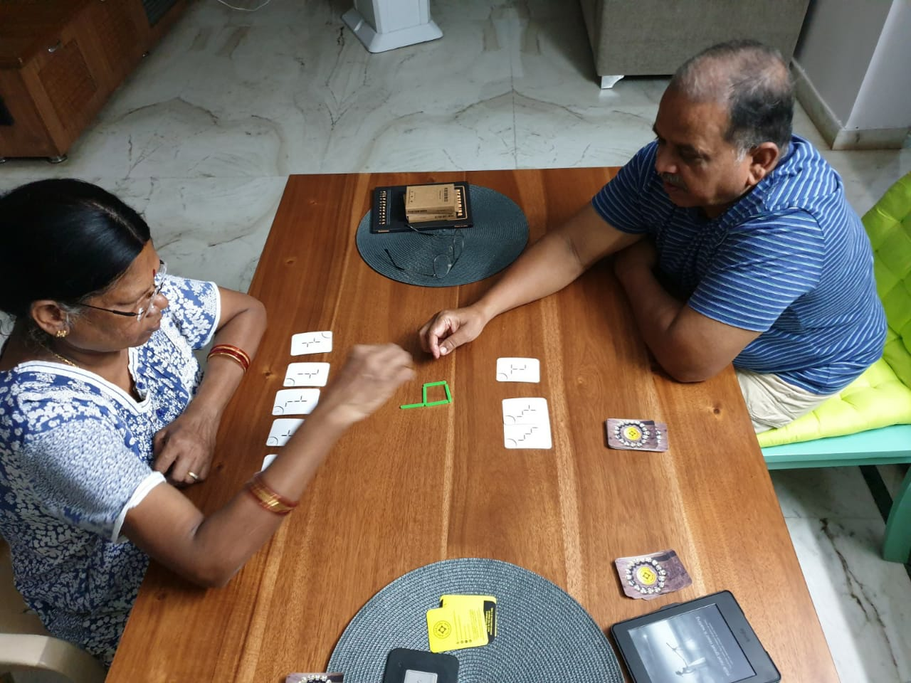 "Parents of my dear friend Preethi are seen playing the card game ""Slick Stick"" gifted to them by her"