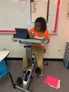 Student practicing math on bike