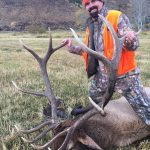 Bill Busbice poses with a bull elk killed on his ranch in Wyoming