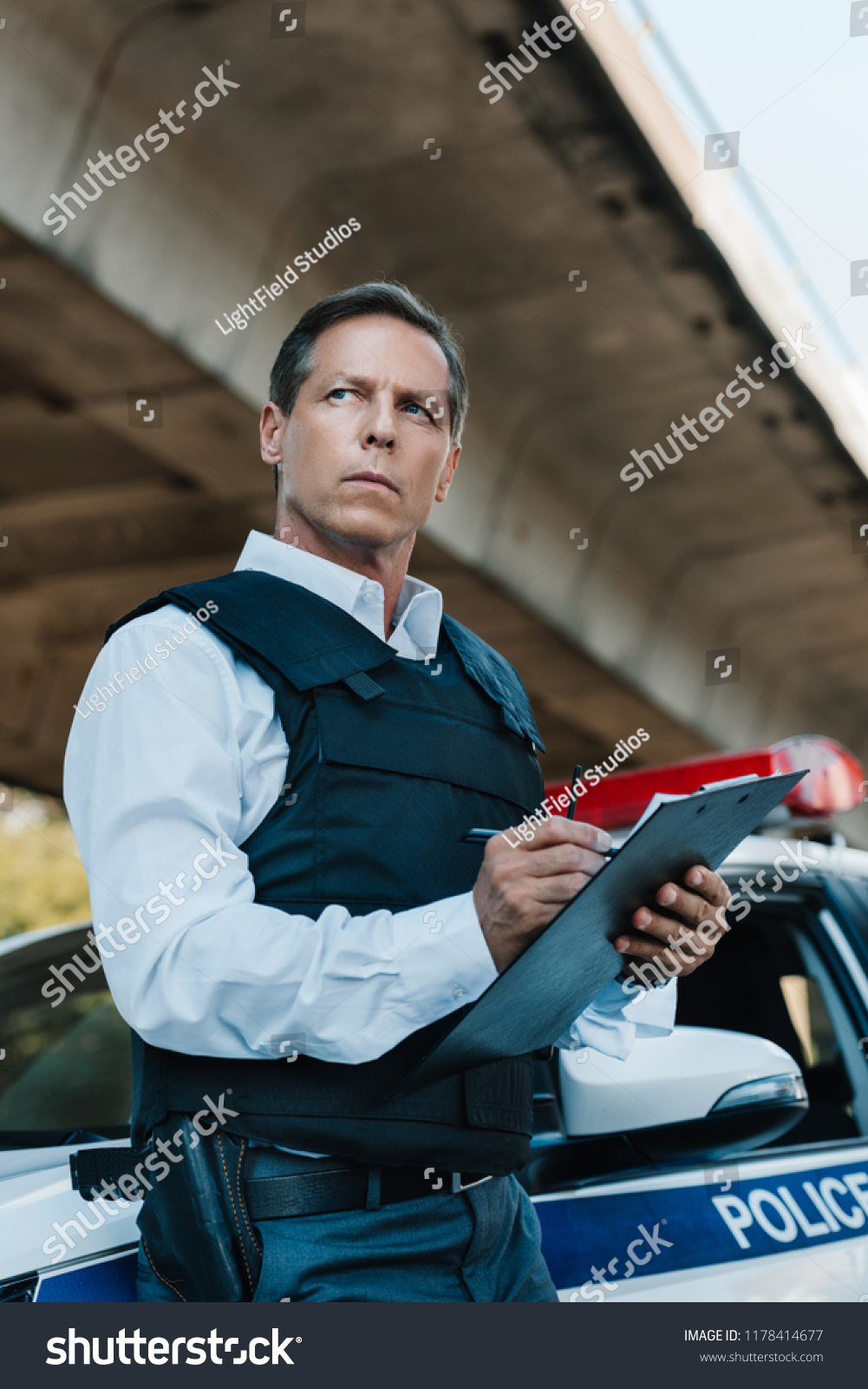 stock-photo-low-angle-view-of-middle-aged-male-police-officer-in-bulletproof-vest-writing-in-clipboard-near-car-1178414677