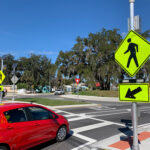 Car stopped at pedestrian crosswalk marked with a traffic sign