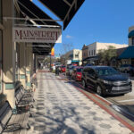Sidewalk with cars parallel parked next to it and a sign for Mainstreet DeLand Association