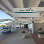 Airport drop off with signs for American Airlines and Delta
