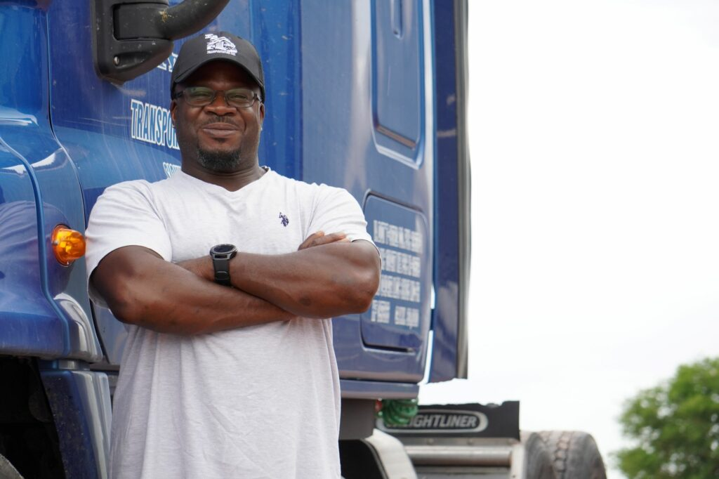 Driver standing next to truck smiling with arms folded