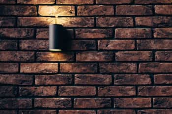 A wall sconce against a brick wall