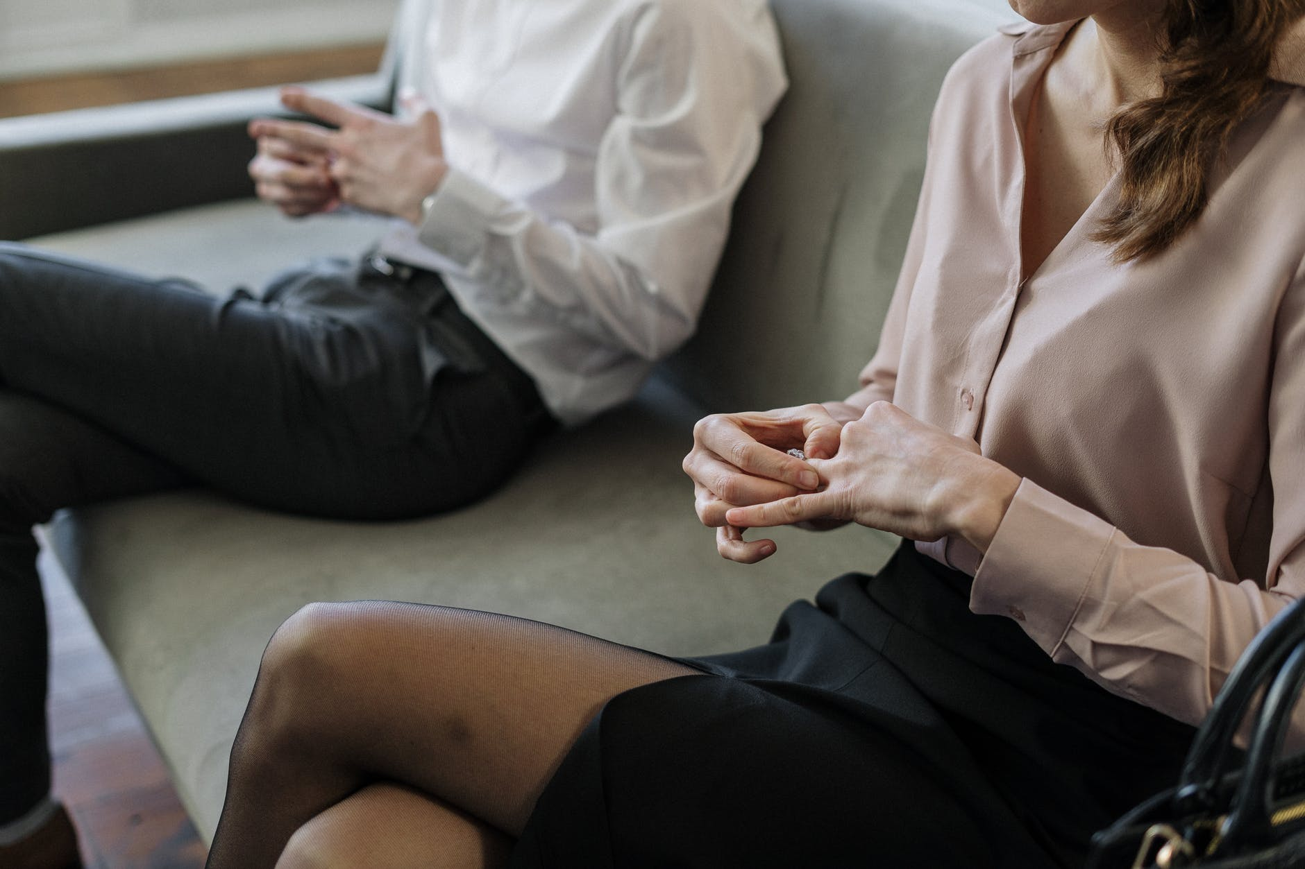 woman in white dress shirt and black skirt sitting on gray couch