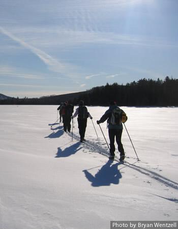 Cross-country skiers skiing across a Maine lake.