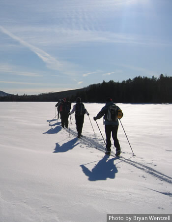 Cross-country skiers skiing across a Maine lake.