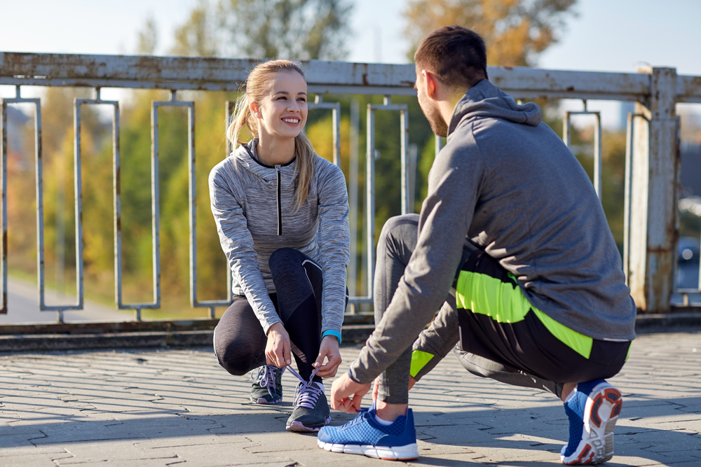 smiling couple tying shoelaces on bridge
