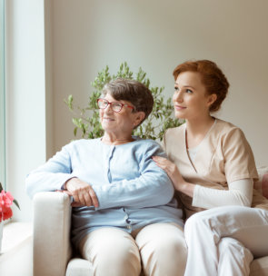 caregiver with elder woman looking out the window