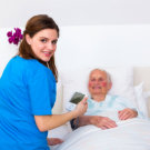 elder woman in bed with caregiver beside her