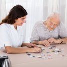 Elder Woman Playing Jigsaw Puzzle On Table With Her Nurse