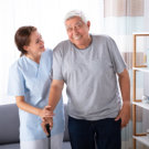 Female Caretaker Assisting Happy Senior Man While Walking At Home