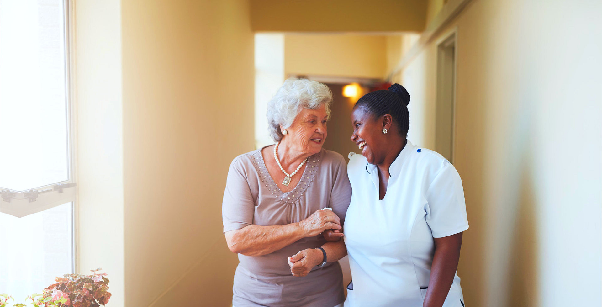 elder woman with caregiver in the hallway talking