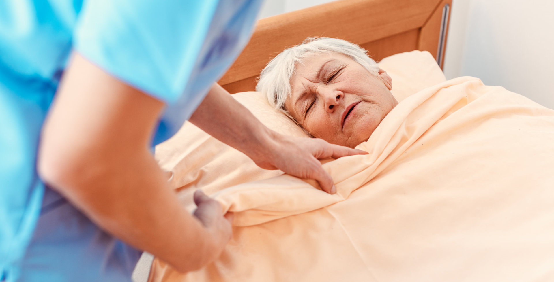 Caregiver pulling blanket over sleeping senior