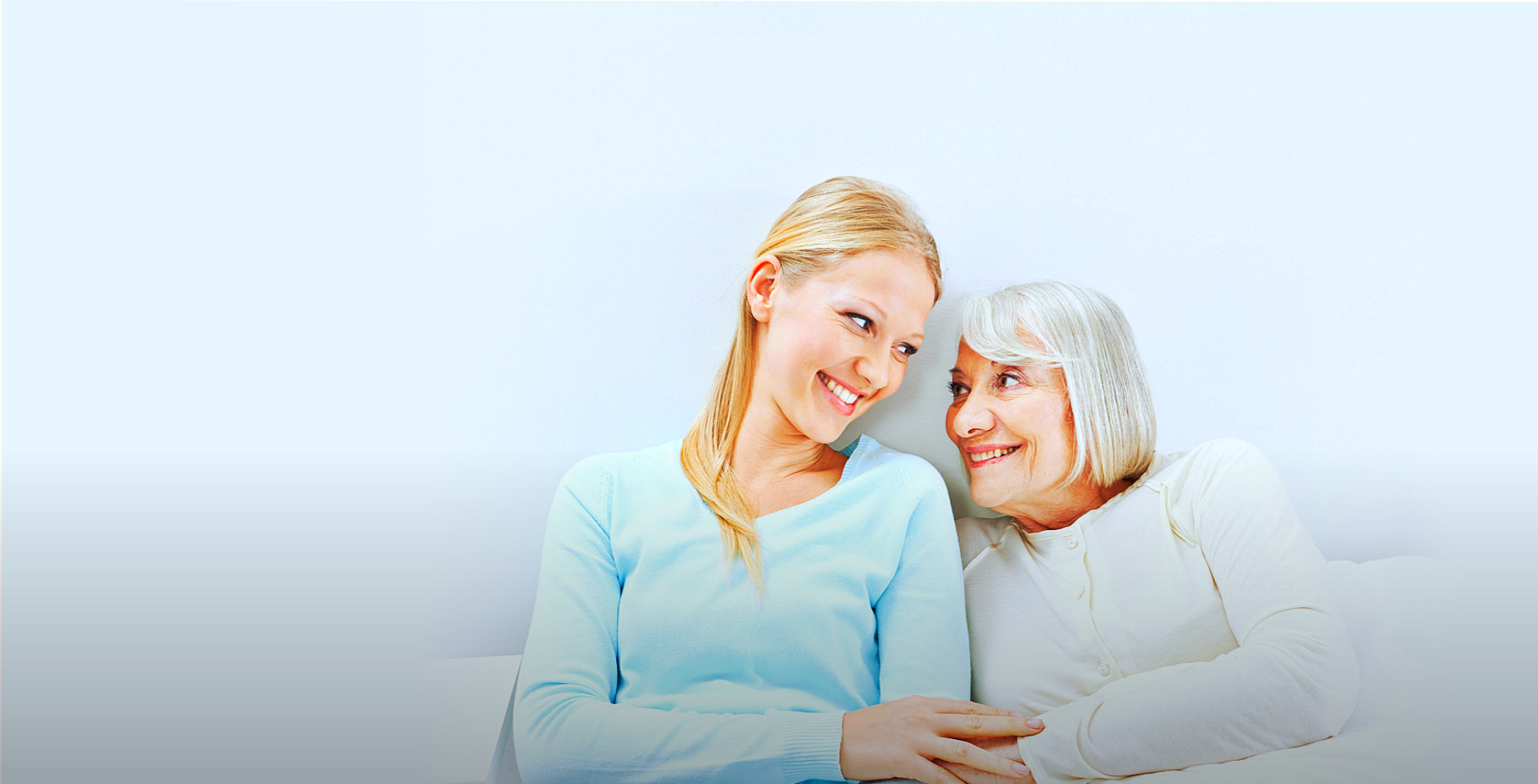 elder woman with caregiver smiling at each other