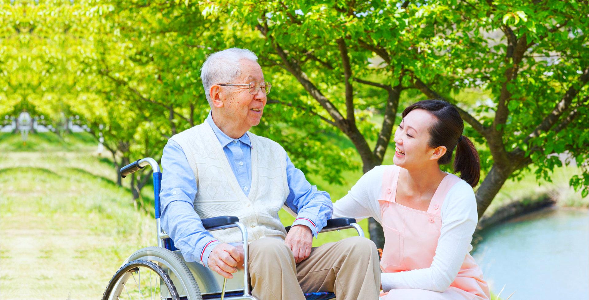 elder man with caregiver at the park