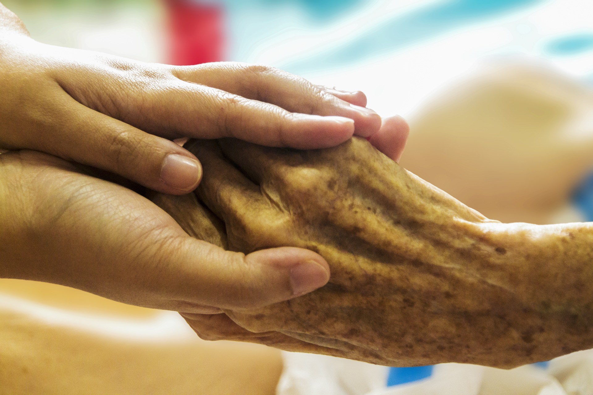 caregiver hold the hand of senior