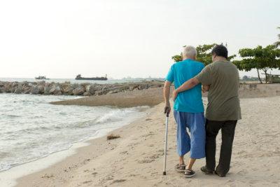man helping senior walk